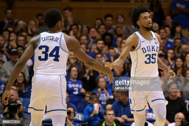 Wendell Carter Jr #34 highfives Marvin Bagley III of the Duke Blue Devils following a dunk by Bagley during their game against the St Francis Red...