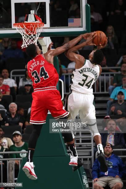Wendell Carter Jr #34 of the Chicago Bulls blocks a shot against Giannis Antetokounmpo of the Milwaukee Bucks during a preseason game on October 3...