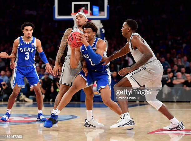 Wendell Moore Jr. #0 of the Duke Blue Devils drives past Galen Alexander and James Akinjo of the Georgetown Hoyas during the second half of their...