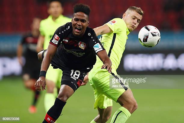 Wendell of Leverkusen is challenged by Alfred Finnbogason of Augsburg during the Bundesliga match between Bayer 04 Leverkusen and FC Augsburg at...