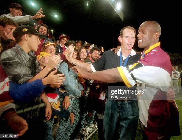 Wendell Sailor of the Broncos and coach Wayne Bennett celebrate victory with fans after the Super League Grand Final between the Brisbane Broncos and...