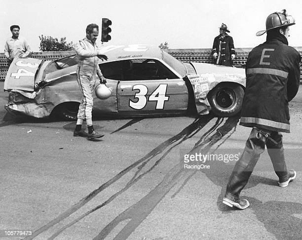 Wendell Scott surveys the damage to his Ford after a practice crash before the Schaefer 300 at Trenton Speedway. Scott tangled with Buddy Baker and...