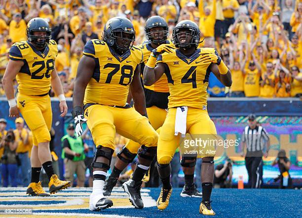 Wendell Smallwood of the West Virginia Mountaineers celebrates with teammates after rushing for a 4 yard touchdown in the first quarter during the...