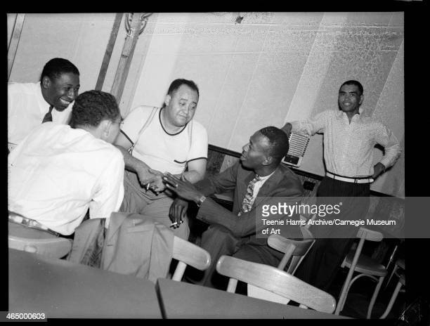 Wendell Smith, William 'Bill' Nunn Sr., Gus Greenlee, Satchel Paige and another man at a table in Crawford Grill No 1, Pittsburgh, Pennsylvania, c...