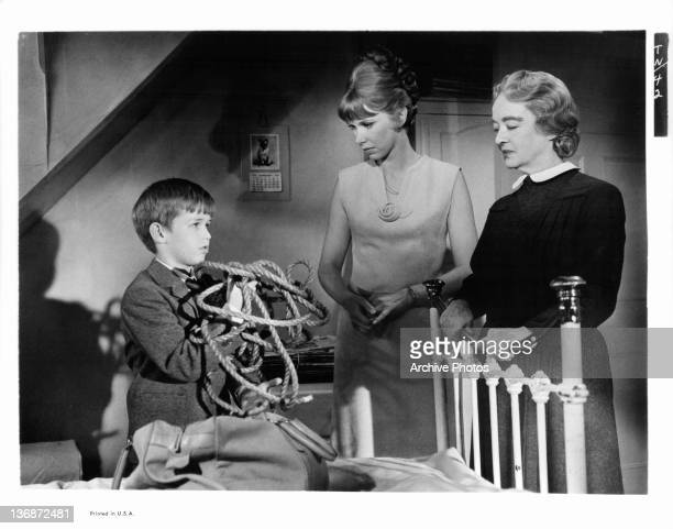 Wendy Craig and Bette Davis looking at boy with rope in a scene from the film 'The Nanny' 1965