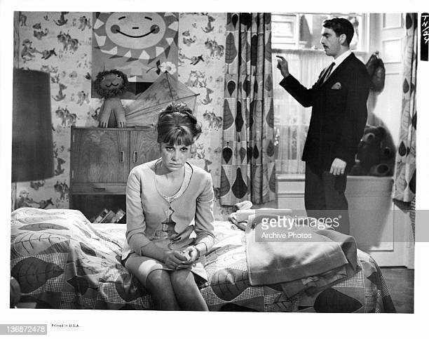 Wendy Craig sitting on bed with tears while James Villiers looks out the window in a scene from the film 'The Nanny' 1965