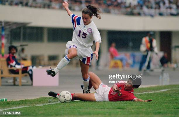 Wendy Gebauer of the United States avoids a tackle by Kyoko Kuroda of Japan during play in the 1991 FIFA Women's World Cup group B match between...
