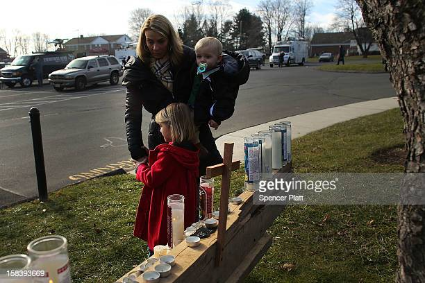 Wendy Goodell and her daughter Amelia and son Luke leave flowers and toys at a memorial outside of a church where residents have come following the...