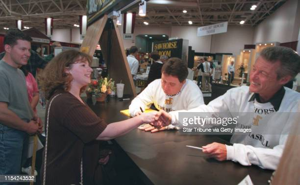 Wendy Hesley of Big Lake shakes hands with Ken Osmond as Jerry Mathers signs an autograph during an session at the Minneapolis home and garden show.