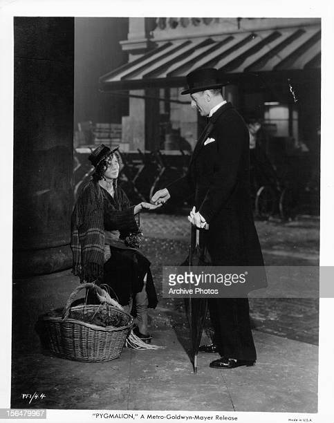 Wendy Hiller is given money from a man in a scene from the film 'Pygmalion', 1938.