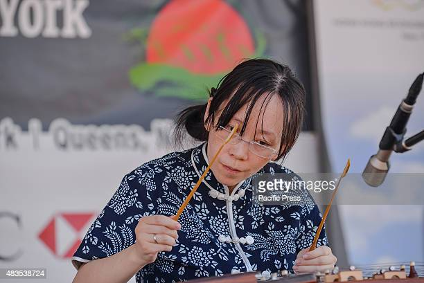 Wendy Li performs on a yangqin a traditional Chinese hammed dulcimer during a concert of traditional music on the festival's second morning The...