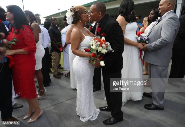 Wendy Ramirez and Anthony Moore kiss as they are wed during a group Valentine's day wedding at the National Croquet Center on February 14 2017 in...