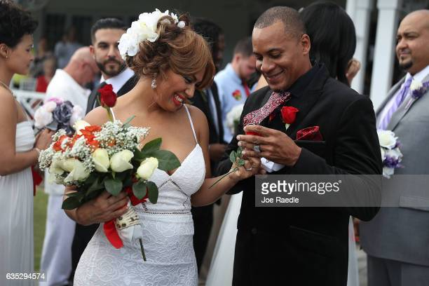 Wendy Ramirez and Anthony Moore prepare to exchange rings during a group Valentine's day wedding at the National Croquet Center on February 14 2017...
