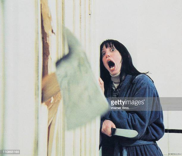 Wendy Torrance played by American actress Shelley Duvall recoils in shock as her husband chops through the bathroom door with a fire axe in a scene...
