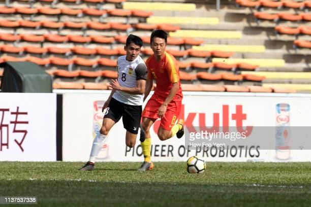Weng Jiabao of China and Aphixay Thqnqkhanty of Laos in action during the AFC U23 Championship qualifier between China and Laos at Shah Alam Stadium...