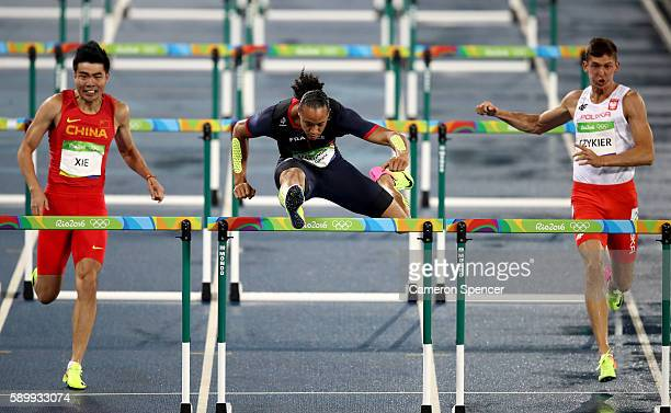 Wenjun Xie of China Pascal MartinotLagarde of France and Damian Czykier of Poland compete during the Men's 110m Hurdles Round 1 Heat 5 on Day 10 of...