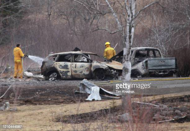 Wentworth volunteer firefighter douses hotspots near destroyed vehicles linked to Sunday's deadly shooting rampage on April 20 2020 in Wentworth...