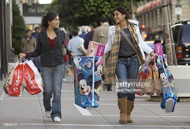Wenzel Gargollo and Carmen Griffith carry their bags on 'Black Friday' November 24 2006 in San Francisco California Many shoppers braved the early...