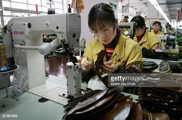 A factory worker stitches leather shoe uppers on a production line at the Kangnai shoe factory in the Chinese city of Wenzhou 30 March 2006 Kangnai...