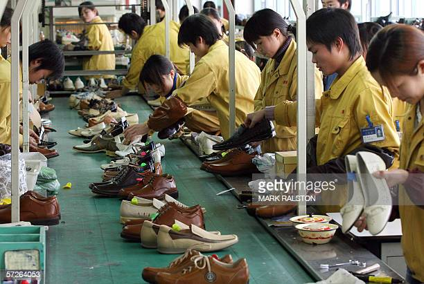 Factory workers check shoes for flaws on a production line at the Kangnai shoe factory in the Chinese city of Wenzhou 30 March 2006 Kangnai is one of...