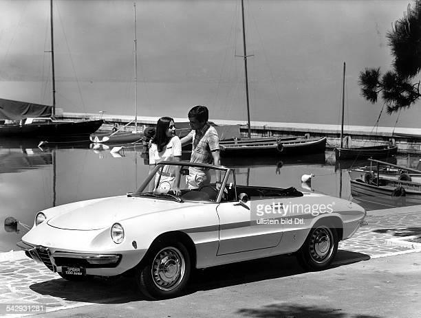 Werbefoto Mann und Frau an lehnen an einem Alfa Romeo Spider 1300 Junior vor Yachthafen Kulisse an einem See Juli 1968