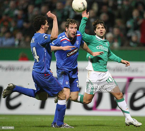 Werder Bremen's Brazilian midfielder Diego vies for the ball against Rangers' defender Kirk Broadfoot and Rangers' Spanish defender Carlos Cuellar...