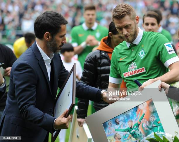Werder's sporting director Thomas Eichin takes player Aaron Hunt's presents and Fair Play award during Hunt's official farewell before the Bundesliga...