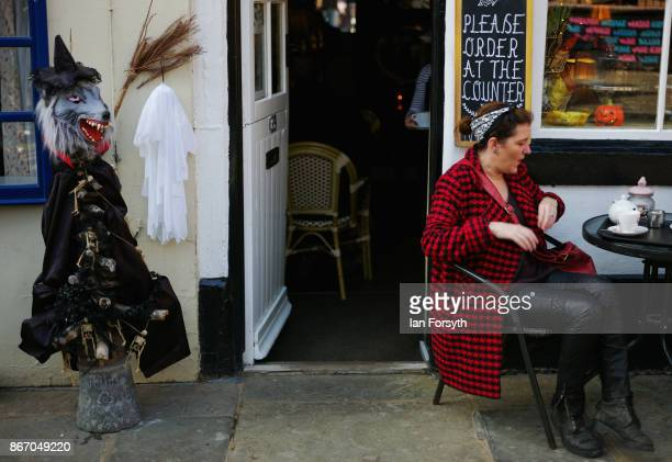 Werewolf is displayed outside a cafe as a woman drinks a coffee during the Whitby Goth Weekend on October 27, 2017 in Whitby, England. The Whitby...