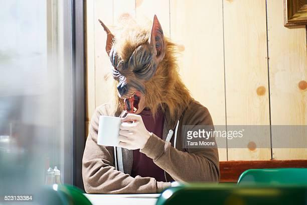 Werewolf with mug in cafe