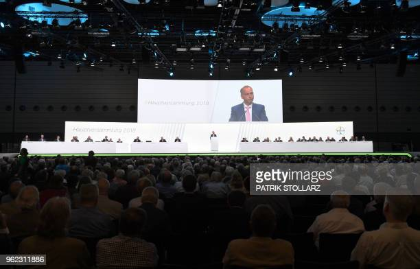 Werner Baumann chairman of German pharmaceutical and chemicals giant Bayer is displayed on a giant screen as he speaks to the shareholders during the...