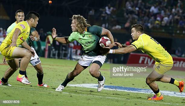 Werner Kok of South Africa is tackled by Allan Faalavaau and Greg Jeloudev of Australia during their final rugby match of the Dubai leg of IRB's...