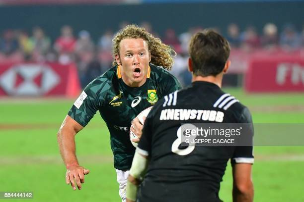 Werner Kok of South Africa vies for the ball with Andrew Knewstubb of New Zealand during their final match in the Men's Sevens World Rugby Dubai...