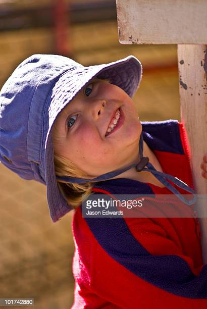A toddler smiles warmly from beneath the brim of a summer hat.