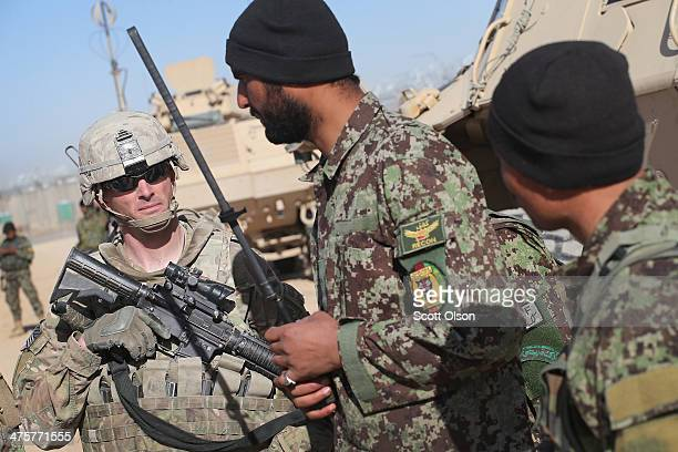 Wes Brockbank from Seattle Washington with the US Army's 4th squadron 2d Cavalry Regiment goes over plans for a joint patrol with soldiers from the...