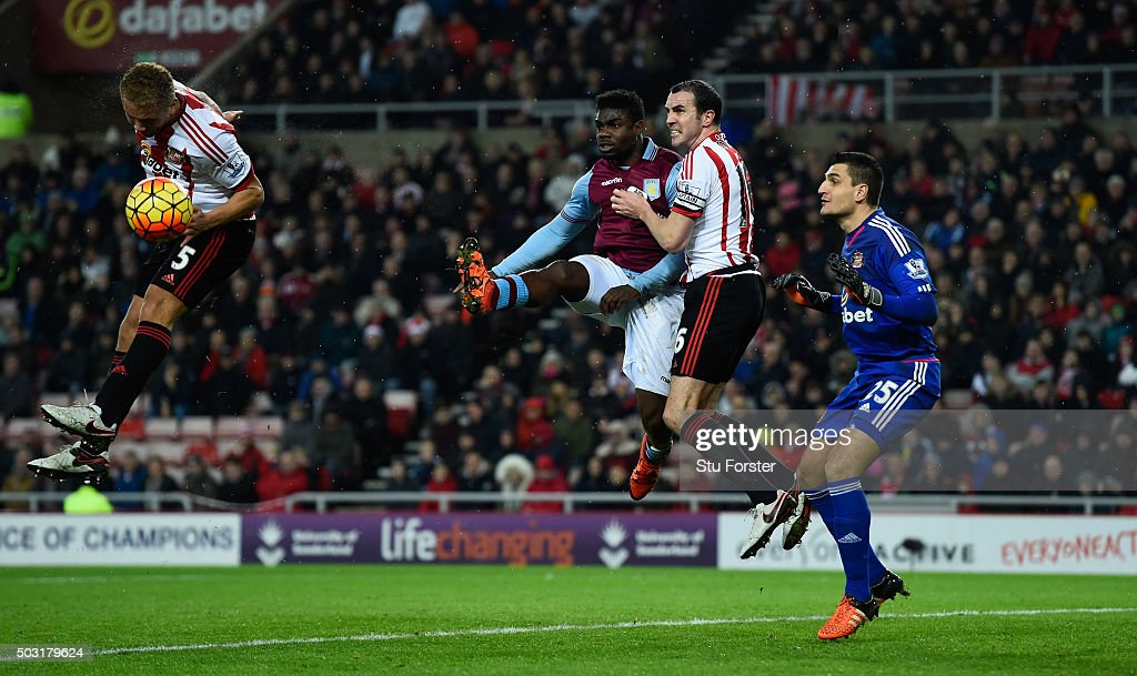 Wes Brown (l) and John O' Shea of Sunderland combine to thwart Michah Richards (c) of Aston Villa during the Barclays Premier League match between Sunderland and Aston Villa at Stadium of Light on January 2, 2016 in Sunderland, England.