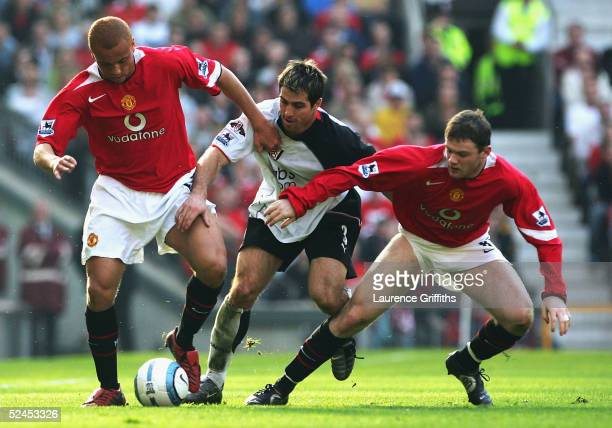 Wes Brown and Wayne Rooney of Manchester United battles for the ball with Carlos Bocanegra of Fulham during the FA Barclays Premiership match between...