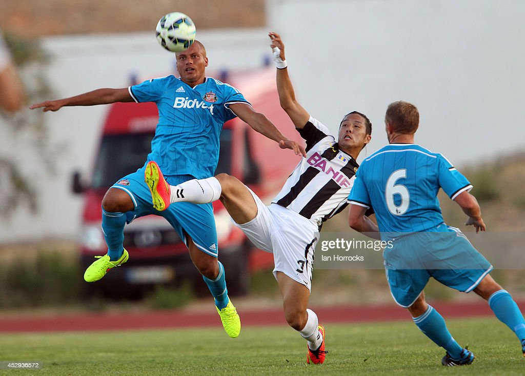 Wes Brown of Sunderland (R) clears ahead of Suk of CD National during a pre-season friendly match between CD National and Sunderland at the Estadio Municipal Albufeira on July 30, 2014 in Albufeira, Portugal.