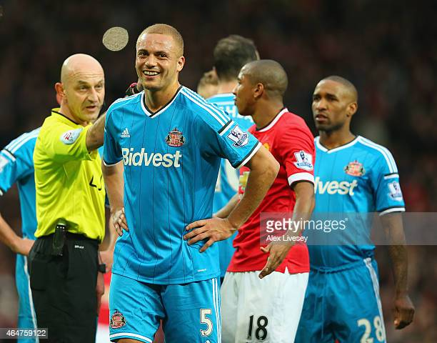 Wes Brown of Sunderland smiles after being shown a straight red card for a challenge on Radamel Falcao García of Manchester United during the...