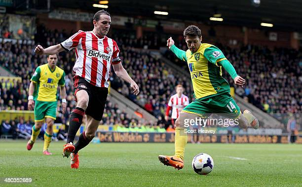 Wes Hoolahan of Norwich attempts to shoot past John O'Shea of Sunderland during the Barclays Premier League match between Norwich City and Sunderland...