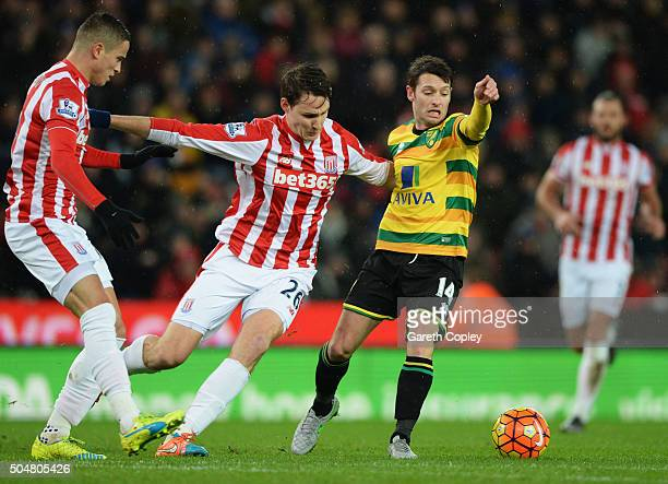 Wes Hoolahan of Norwich City and Philipp Wollscheid of Stoke City compete for the ball during the Barclays Premier League match between Stoke City...