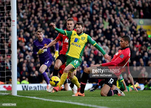 Wes Hoolahan of Norwich City is challenged by Chris Smalling of Manchester United as he shoots during the Barclays Premier League match between...