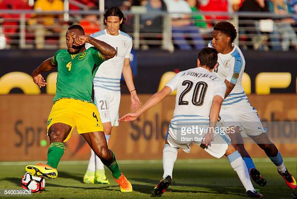 Wes Morgan of Jamaica fights for the ball with Alvaro Gonzalez and Abel Hernandez of Uruguay during a group C match between Uruguay and Jamaica at...