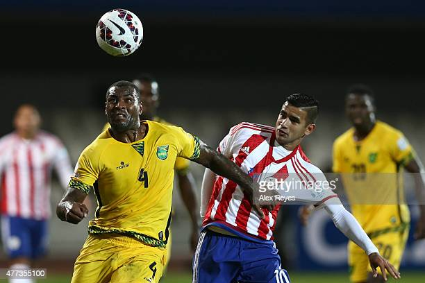 Wes Morgan of Jamaica fights for the ball with Derlis Gonzalez of Paraguay during the 2015 Copa America Chile Group B match between Paraguay and...