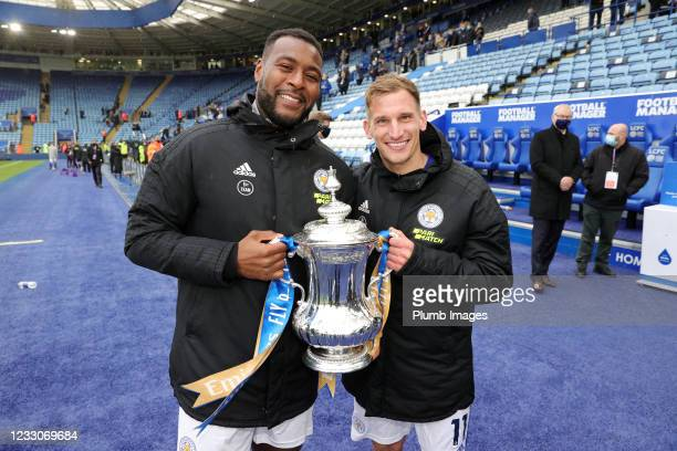 Wes Morgan of Leicester City and Marc Albrighton of Leicester City pose with the FA Cup trophy during a lap of the pitch after the Premier League...