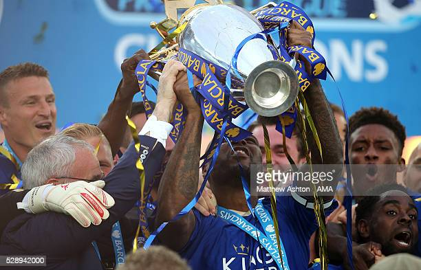 Wes Morgan of Leicester City lifts the Premier League Trophy as his teammates celebrate becoming Premier League Champions for the 2015/16 Season at...