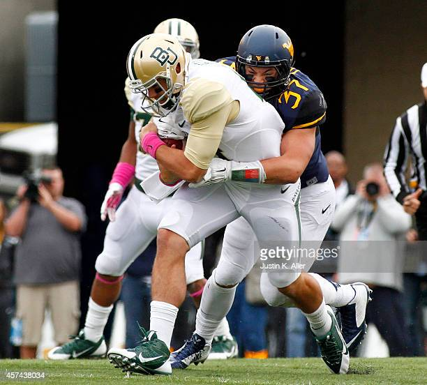 Wes Tonkery of the West Virginia Mountaineers tackles Bryce Petty of the Baylor Bears in the first half during the game on October 18 2014 at...
