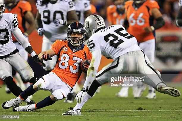 Wes Welker of the Denver Broncos completes a first down pass reception against DJ Hayden of the Oakland Raiders at Sports Authority Field at Mile...