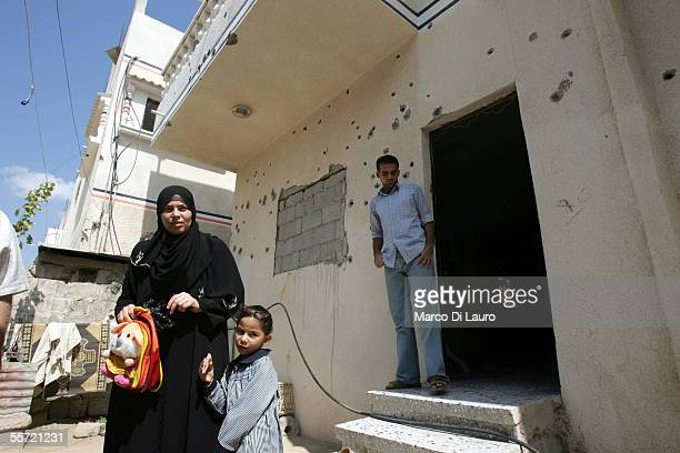 Wesal Kishta 32yearsold holds her daughter Smar 4yearsold as they stand next to a family friend Muhamad 23yearsold in front of her bullet hole...