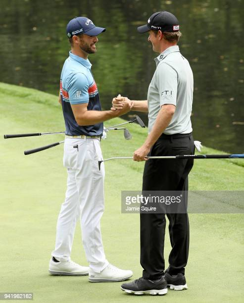 Wesley Bryan of the United States shakes hands with Webb Simpson of the United States during the Par 3 Contest prior to the start of the 2018 Masters...