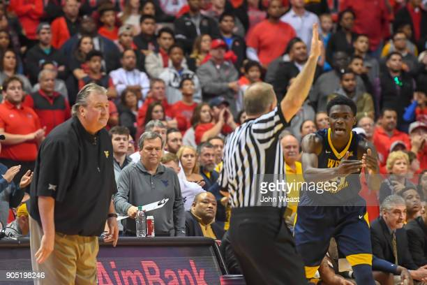 Wesley Harris of the West Virginia Mountaineers calls time out as head coach Bob Huggins of the West Virginia Mountaineers looks on during the game...